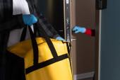 Vágott kilátás a szállító férfi kezében termo táska közelében nő latex kesztyű nyitó ajtó