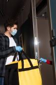 Oldalnézet futár orvosi maszk tartja termo táska közelében nő latex kesztyű nyitó ajtó