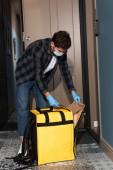 Futár orvosi maszk és latex kesztyű tartó csomag és termo táska közelében nyitott ajtó bejáratánál