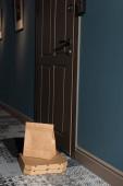 Csomagok és pizzás dobozok a bejárati ajtó közelében a padlón