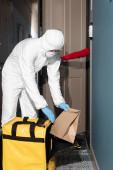 Szállító férfi vegyvédelmi ruha és orvosi maszk vesz csomag termo táska közelében nő nyitó ajtó