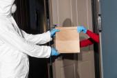 Oldalsó nézet férfi vegyvédelmi ruha és orvosi maszk így csomag nő latex kesztyű közelében nyitott ajtó