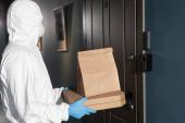Oldalnézet futár vegyvédelmi ruha és orvosi maszk holding csomag és pizza dobozok ajtó közelében