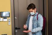 Junger Mann mit medizinischer Maske benutzt Händedesinfektionsmittel in der Nähe der Wohnungstür