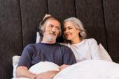 šťastná zralá žena dotýkající se vlasů manžela a usmívající se v posteli