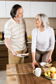 happy mature woman looking at husband and touching jar with jam