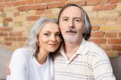 šťastný muž středního věku a žena při pohledu na kameru