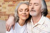 šťastný muž středního věku a žena se zavřenýma očima