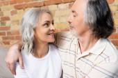 šťastný muž středního věku a žena při pohledu na sebe