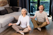 Photo relaxed mature couple with closed eyes sitting in lotus pose