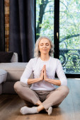 relaxed mature woman with closed eyes and praying hands sitting in lotus pose
