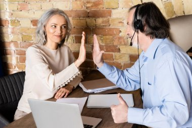 Happy mature woman giving high five to husband in headset showing thumb up near laptop on table stock vector