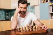 Photo Selective focus of thoughtful man sitting near chess on chessboard on table