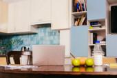 Fotografie Papíry s notebookem v blízkosti ovoce a snídaně na stole v kuchyni