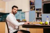 Boční pohled pohledný na volné noze v košili a kalhotky při pohledu na kameru v blízkosti notebooku a snídaně na kuchyňském stole