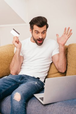 Shocked man looking at laptop while holding credit card on couch stock vector