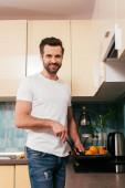 Hezký muž se usmívá na kameru při vaření snídaně v kuchyni