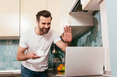 Selective focus of smiling man holding cup of coffee and having video call on laptop in kitchen stock vector