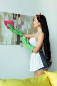 Photo Side view of sexy girl cleaning painting with rag and spray bottle