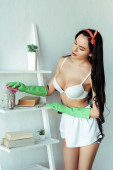 Photo Seductive woman in rubber gloves cleaning decorative statuette on rack at home
