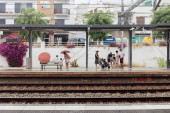 CATALONIA, SPAIN - APRIL 30, 2020: People with umbrellas waiting on train station