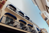 Low angle view of tables and chairs on balcony of building with blue sky at background in Catalonia, Spain