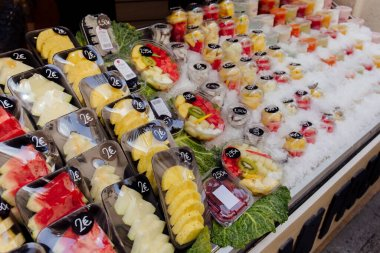 Fresh fruits in containers with price tags in ice on counter of outdoor shop