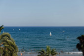 CATALONIA, SPAIN - APRIL 30, 2020: People resting on beach with palm trees and yachts in sea at background