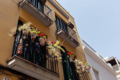 Nízký úhel pohledu na kvetoucí květiny v květináčích na balkóně domu v Katalánsku, Španělsko