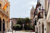 BARCELONA, SPANYOLORSZÁG - Április 30, 2020: La Senyera zászlók épületek városi utcában templom San Bartolome és Santa Tecla és kék ég a háttérben