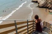 KATALONIE, ŠPANĚLSKO - 30. dubna 2020: Selektivní zaměření ženy stojící na schodišti s písčitou pláží a mořem v pozadí