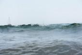 Povrchová hladina jachet v moři s vlnami a modrá obloha na pozadí, Katalánsko, Španělsko