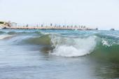 Selektivní zaměření vln na mořském pobřeží s molem a palmami na pozadí, Katalánsko, Španělsko