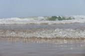Selektivní zaměření vlny na mokré písečné pláži s modrou oblohou na pozadí