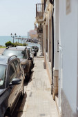 Fotografie Urban street with row of cars, buildings and sea with blue sky at background in Catalonia, Spain