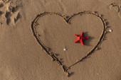 Top kilátás vörös tengeri csillag a szív jel a homokon