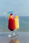 Two glasses of cocktails with drinking straws on table and sea with sky at background