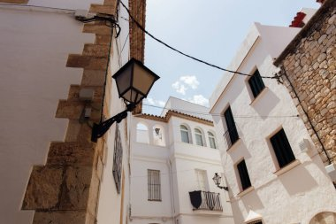 Low angle view of lantern on angle of building facade with blue sky at background, Catalonia, Spain