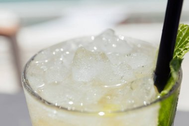 Selective focus of glass of cocktail with ice cubes and mint leaf