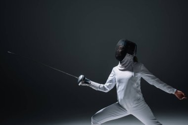 Fencer in fencing mask exercising on black background stock vector