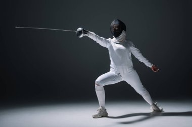 Swordswoman in fencing mask and suit holding rapier on white surface on black background