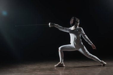 Fencer in fencing mask doing lunge while training with rapier on black background stock vector