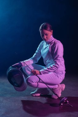 Beautiful fencer holding fencing mask and rapier on black background with lighting