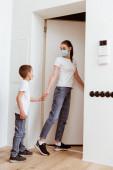 Mutter und Sohn in Schutzmasken halten sich vor Tür im Hausflur an den Händen