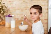 Boční pohled na chlapce při pohledu na kameru při jídle cereálií v kuchyni