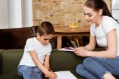 Usmívající se matka drží barevné tužky v blízkosti syna kreslení na papíře na pohovce