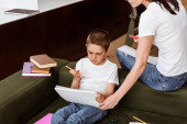 Matka drží skicák, zatímco syn s barevnou tužkou sedí v blízkosti knih na gauči