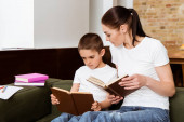 Matka a syn čtení knih v blízkosti papíru a barevné tužky na gauči