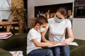 Anya és a gyerek orvosi maszkok rajz színes ceruzák papíron közel könyvek kanapén