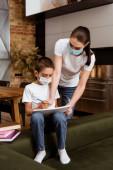 Anya orvosi maszkban kezében vázlatfüzet közelében fia ceruzával és könyvek kanapén otthon